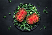 Half-cut red tomato on kale salad
