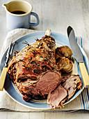 Roast leg of lamb with roast onions and jug of gravy