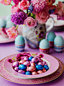 Easter eggs in a pink bowl with boiled eggs and a vase of Spring flowers on a table
