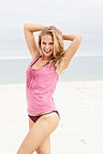 Junge Blonde Frau im rosa Top und Bikini am Strand