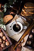 Eine Taste Kaffee auf Vintage Karte, umgeben von Früchtebrotscheiben und Nüssen