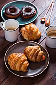 Zwei Becher Kaffee, Croissants und Donuts