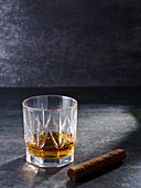 Crystal glass with whiskey drink and thick cigar