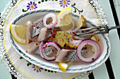 Pickled herring with red onions, bay leaves and lemon