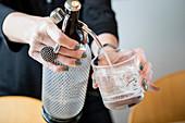 Wasser aus Sodaflasche in Glas füllen