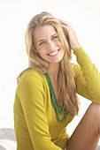 Junge blonde Frau mit olivfarbenem Shirt am Strand