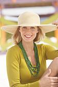 Junge blonde Frau mit olivfarbenem Shirt und beigem Sonnenhut am Strand