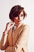 Junge Frau in brauner Lederjacke und mit Modeschmuck