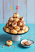 Profiterol with whipped cream, chocolate and almonds for new year