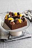 A square Sachertorte (rich Austrian chocolate cake) with black chocolate truffles, chocolate cream and oranges