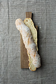 A light baguette, halved lengthways, on a wooden board