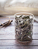 Glass of dried sage leaves