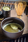 Green matcha tea with whisk