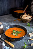 Roasted pepper and tomato soup with greek basil leaves and sourdough bread
