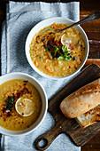 Two bowls of lentil soup on blue tablecloth