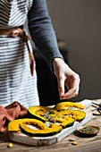 Woman flavouring pumpkin slices with origan and rosemary