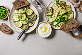 Variety of grilled zucchini salad with green pea, yogurt dip, garlic and rye sliced bread in spotted ceramic plates