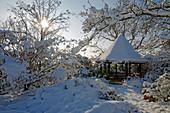 Verschneiter Pavillon im winterlichen Garten