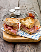 Toasted bacon sandwich with crusty white bread and tomato ketchup