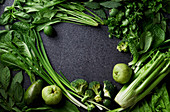 Variety of green vegetables and fruits on dark concrete background