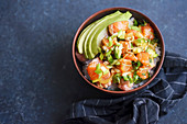 Poke bowl with raw marinated salmon, cucumbers and avocado