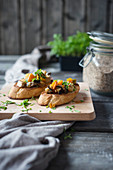 Grilled baguette slices with oven-roasted vegetables (carrots, aubergines, courgettes, cauliflower) and sesame seeds