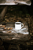 An enamel mug of coffee on a rustic wooden bench