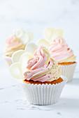 Kokos-Cupcakes mit zweifarbiger Buttercreme und weissen Schokoladenherzen