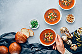 Vegan tomato soup served in three white bowls accompanied by bread rolls, roasted garlic, croutons and peas