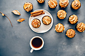 Apple muffins on a dark grey backdrop accompanied by fall leaves, a cup of tea, a plate and cinnamon sticks