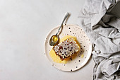Organic honey in honeycombs with spoon in spotted ceramic plate on linen cloth over white marble background