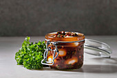 Opened Jar with homemade pickled marinated quail eggs in tomato and olive oil sauce with anchovies and fresh parsley