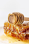 Organic honey in honeycombs flowing from wooden dipper on white marble background