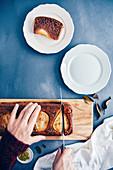 Kastenkuchen mit Birnen auf Holzbrett in Stücke schneiden