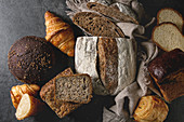 Variety of fresh baked rye, spelled, wheat craft artisan bread, whole and sliced