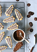 Christmas tree shaped cookies, coated in brown chocolate and decorated with white icing