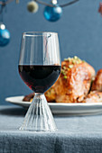 A red wine glass in front of a Christmas roast on a blue tablecloth