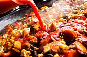Vegane Paella zubereiten: Tomatensauce zufügen