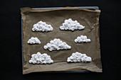 Ungebackene Baiser-Wolken auf Backblech mit Backpapier