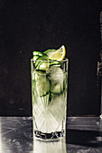 Cucumber gin with tonic in a crystal glass against a dark background