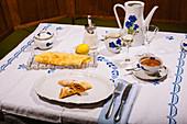 Pfannkuchen mit Puderzucker auf gedecktem Tisch, im Stil der 70er Jahre