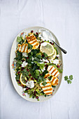 Bulgur salad with grilled halloumi, pomegranate seeds, celery, parsley and a yoghurt dip