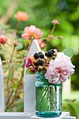 Blüte von Rose 'Shropshire Lad' und Brombeeren im Glas