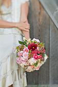 Frau hält Strauß mit Dahlienblüten und Rosen