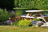 Kräuterbeet an kleiner Terrasse mit Tisch-Bank-Kombination