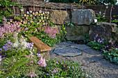Kleine Schattenterrasse mit Steinblöcken, Brennholz und Astilben