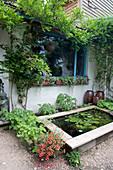 Terrasse mit Teichbecken und Blauregen am Vordach