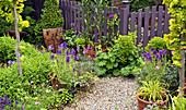 Garten mit Stauden, Kiesweg und Gartenzaun mit Gartentor