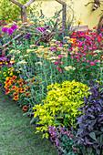 Buntes Beet im bienenfreundlichen Garten, Bienenskulptur aus Zweigen