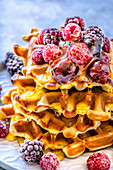 Home-made Belgian waffles baked in an electric waffle-iron with berries and maple syrup